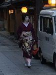 A geisha walking to an liquor store