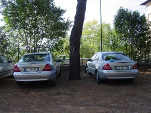 Which car is ours? The Mercedes on the left or the one on the right with a colorful package of pastries on the trunk?