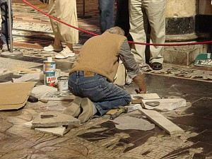 An artisan repairing the floor of the Duomo, from the rear