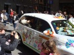 A decorated taxi with a pretty girl giving out candy!