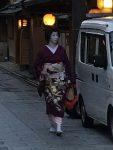 A geisha walking to an liquor store